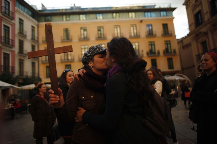 Two women kiss during a protest in front of the Malaga Cathedral in Malaga, southern Spain, January 23, 2014. Protesters were called by lesbian, gay, feminist, bisexual and transsexual associations to kiss in public against what they said were religious homophobic statements made by new Spanish Cardinal Fernando Sebastian Aguilar, appointed by Pope Francis. The cardinal had said homosexuality was a physical defect which could be cured with the right treatment, during an interview with a local newspaper. (REUTERS/Jon Nazca)