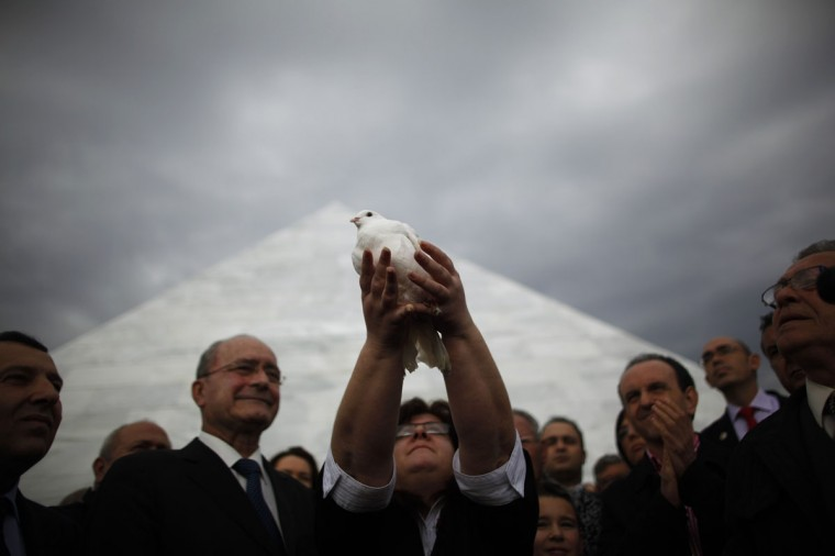 A woman releases a pigeon during the opening ceremony of a mausoleum (rear) built in memory of Republicans killed during and after the 1936-1939 Spanish Civil War at the cemetery of San Rafael in Malaga, southern Spain, January 11, 2014. The eight-metre tall monument is made of marble slabs engraved with the names of over 4,400 war victims. It contains 2,840 boxes of humans remains, which have been recovered from open mass graves in the cemetery of San Rafael. (REUTERS/Jon Nazca)