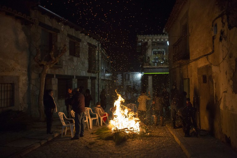 "People gather around a fire during the ""Luminarias"" annual religious celebration on the night before Saint Anthony's, patron of animals, in the village of San Bartolome de los Pinares, about 100 km (62 miles) northwest of Madrid, January 16, 2014. According to tradition that dates back 500 years ago, people rode their horses through the narrow cobblestone streets of this small village to purify the animals with the smoke of the bonfires. Picture taken January 16, 2014. (REUTERS/Juan Medina)"
