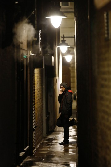 A man smokes in an alley behind his place of work in London January 17, 2014. Fifty years after the first U.S. surgeon general's report declared smoking a hazard to human health, the tally of smoking-related effects keeps rising, with liver and colorectal cancers, diabetes, rheumatoid arthritis and even erectile dysfunction joining the list, according to a report released on Friday. REUTERS/Luke MacGregor