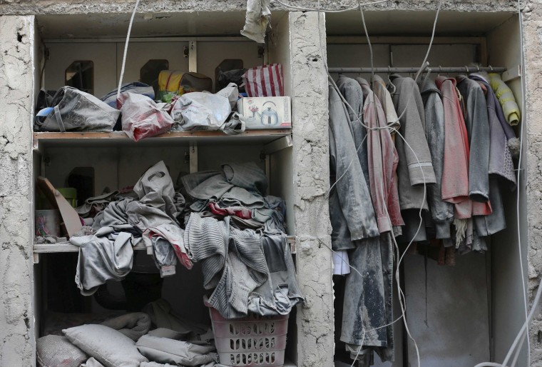 Dust covers clothes at a site hit by what activists said was an airstrike by forces loyal to Syrian President Bashar al-Assad in the Duma neighbourhood of Damascus January 7, 2014. (Bassam Khabieh/Reuters)