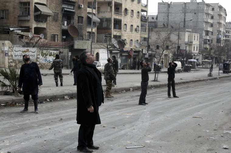 Residents lookout for warplanes after what activists said was an air strike by forces loyal to Syria's president Bashar Al-Assad in the Al-Ansari neighborhood of Aleppo January 19, 2014. (Ammar Abdullah/Reuters)