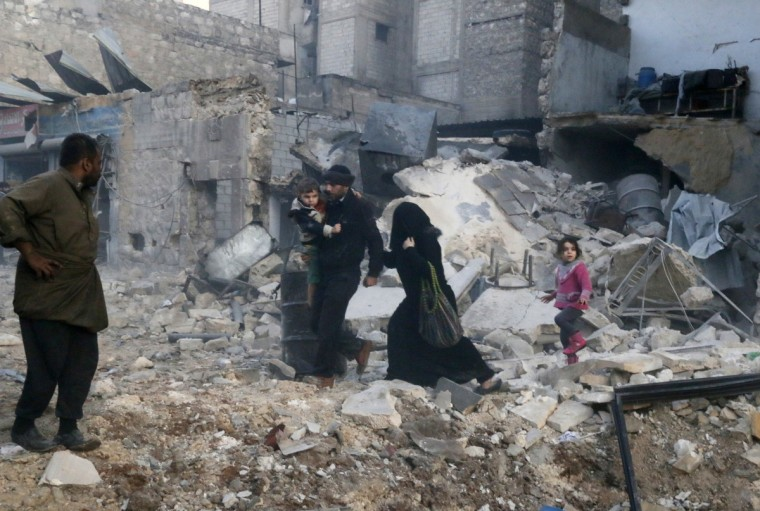 People walk on rubble of collapsed buildings at a site hit by what activists said was barrel bombs dropped by government forces in Aleppo's Dahret Awwad neighborhood. (Saad AboBrahim/Reuters)