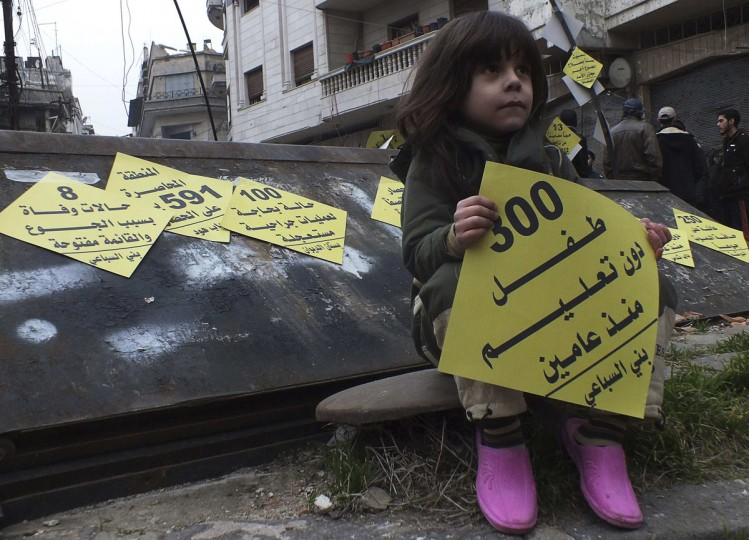 "A girl carries a sign that reads '300 children without education since two years' during a campaign organised by activists in the besieged area of Homs, January 22, 2014. Activists erected yellow signs in the besieged area of Homs as part of a campaign called ""Yellow covers the besieged area of Homs"". The campaign aims to shed light on what is happening inside the area which is suffering severe food and medical shortages, and calling on humanitarian organisations to help and evacuate the families and wounded people. (REUTERS/Yazan Homsy)"