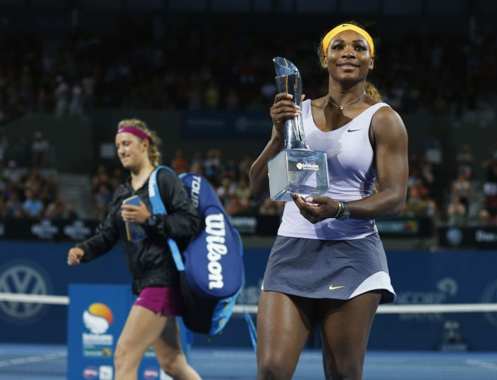 Serena Williams of the U.S. holds up the Brisbane International women's singles trophy after defeating Victoria Azarenka of Belarus (L) as she walks off the court in Brisbane, January 4, 2014. (REUTERS/Jason Reed)
