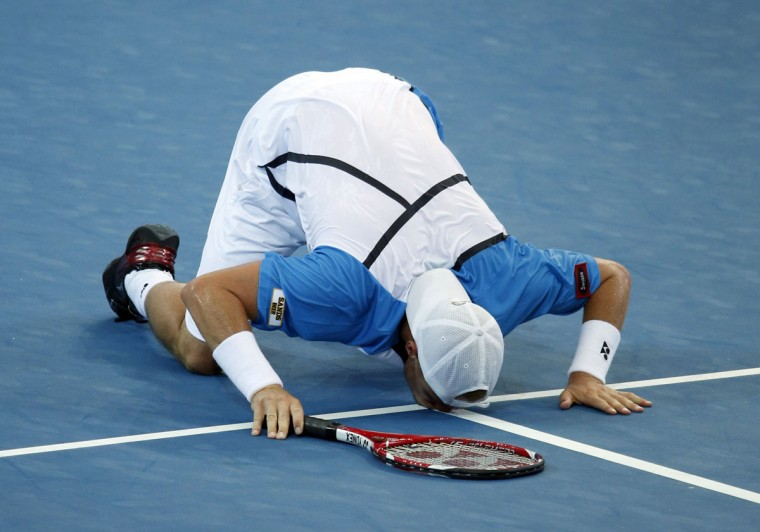 Lleyton Hewitt of Australia kisses the court as he celebrates his win against Kei Nishikori of Japan during their men's singles semi-final match at the Brisbane International tennis tournament in Brisbane, January 4, 2014. (REUTERS/Jason Reed )