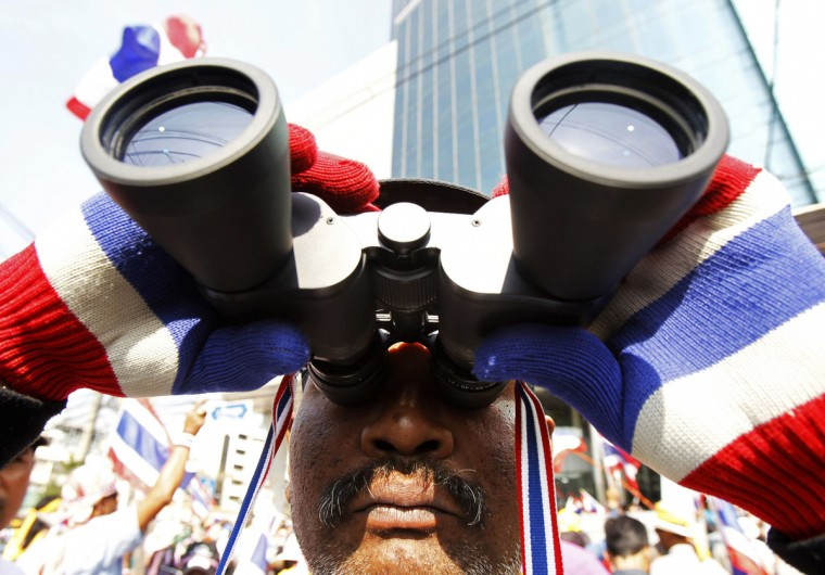 An anti-government protester uses a pair of binoculars during a rally in central Bangkok January 16, 2014. Protesters in Thailand trying to paralyse ministries to force the government to resign said they would target revenue offices on Thursday, but their numbers appeared to be dwindling and ministers say the movement could be running out of steam. (REUTERS/Chaiwat Subprasom)