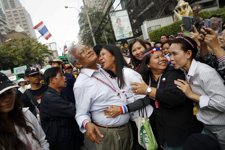 Protest leader Suthep Thaugsuban (C) is hugged by an anti-government protester as he leads a march through Bangkok's business district January 23, 2014. The government declared a 60-day state of emergency from Wednesday hoping to prevent an escalation in protests now in a third month. (REUTERS/Damir Sagolj)