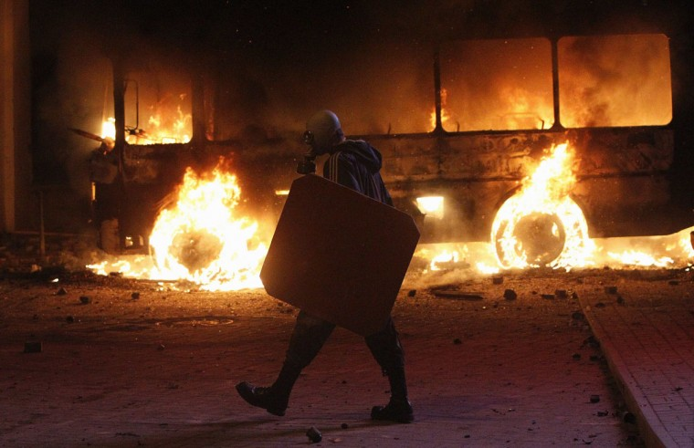 A pro-European integration protester walks past a burning police bus during a rally near government administration buildings in Kiev, January 19, 2014. Protesters attacked riot police with sticks in Kiev on Sunday and tried to overturn a bus blocking their path to parliament, as up to 100,000 Ukrainians massed in defiance of sweeping new laws aimed at stamping out anti-government demonstrations. (Gleb Garanich/Reuters)