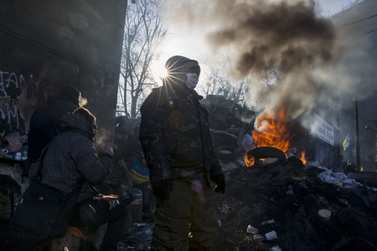 Anti-government protesters gather at an open fire site as temperatures stand at minus 20 degrees Celsius (minus 4 degrees Fahrenheit) at a barricade near Independence Square in Kiev, January 30, 2014. Ukrainian President Viktor Yanukovich has gone on sick leave with a respiratory ailment, his website said on Thursday, with the issue of a new prime minister still undecided. Yanukovich's prime minister, Mykola Azarov, resigned on Tuesday in the midst of mass street unrest and the president has yet to appoint a successor. Serhiy Arbuzov, who was Azarov's first deputy, has stepped in as interim prime minister. REUTERS/Thomas Peter