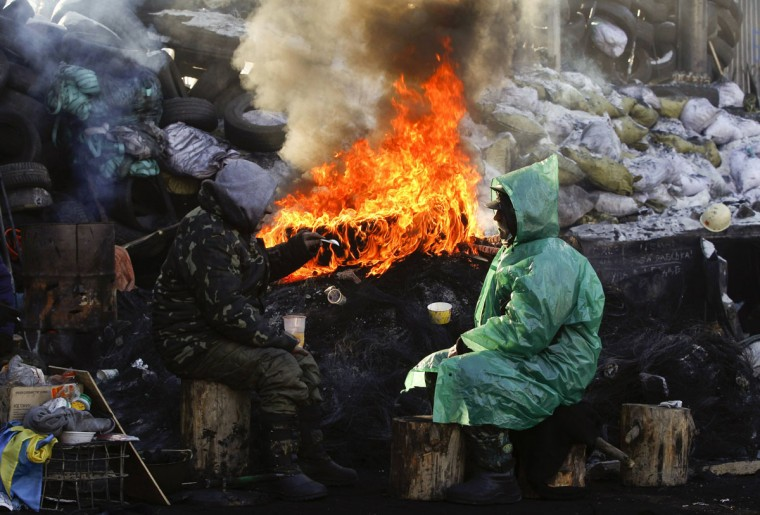 Demonstrators have a chat near a fire at a barricade erected by anti-government protesters near the site of clashes with riot police, with the air temperatures around minus 20 degrees Celsius (minus 4 degrees Fahrenheit), in Kiev, January 30, 2014. Ukrainian President Viktor Yanukovich has gone on sick leave with a respiratory ailment, his website said on Thursday, with the issue of a new prime minister still undecided. Yanukovich's prime minister, Mykola Azarov, resigned on Tuesday in the midst of mass street unrest and the president has yet to appoint a successor. Serhiy Arbuzov, who was Azarov's first deputy, has stepped in as interim prime minister. REUTERS/Vasily Fedosenko