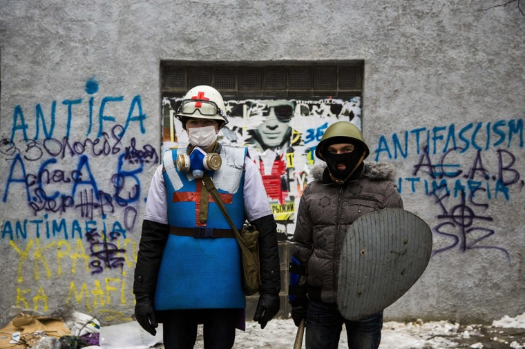 A medic of the anti-government protest camp (L) poses for a portrait with his security guard at the barricades near the site of clashes with riot police in Kiev January 28, 2014. Ukrainian Prime Minister Mykola Azarov resigned on Tuesday while deputies loyal to President Viktor Yanukovich, acting to calm violent street protests, back-tracked and overturned anti-protest laws they rammed through parliament 12 days ago. (Thomas Peter/Reuters)