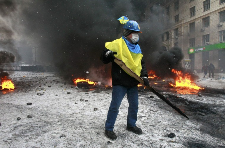 A pro-European protester holds a half burned piece of wood during clashes with riot policemen in Kiev January 22, 2014. The European Union threatened on Wednesday to take action against Ukraine over its handling of anti-government protests after three people died during violent clashes in Kiev. (REUTERS/Gleb Garanich)