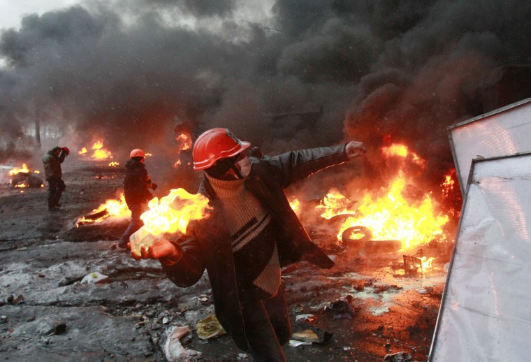 "A pro-European protester throws a Molotov cocktail towards riot police near burning tyres during clashes in Kiev January 22, 2014. Ukraine's prime minister denounced anti-government protesters as ""terrorists"" on Wednesday, but in what appeared to be his first real move to end weeks of unrest President Viktor Yanukovich held talks with opposition leaders. (REUTERS/Gleb Garanich)"