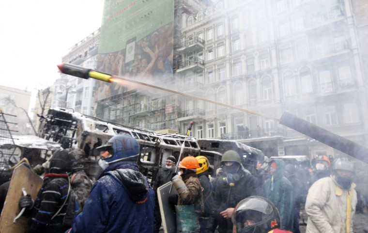 "Pro-European protesters launch a pyrotechnic pistol towards riot police during clashes in Kiev January 22, 2014. Ukrainian Prime Minister Mykola Azarov said on Wednesday anti-government protests had brought ""terrorists"" on to the streets and warned that all ""criminal actions"" would be punished. (REUTERS/Vasily Fedosenko)"