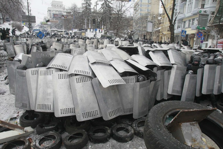 "Interior Ministry members take cover behind shields as pro-European protesters erect a barricade during a rally in Kiev January 22, 2014. The European Union condemned the escalating violence in Ukraine on Wednesday and called on the country's government and opposition to ""engage in a genuine dialogue"" after three people were killed during protests. (REUTERS/Gleb Garanich)"