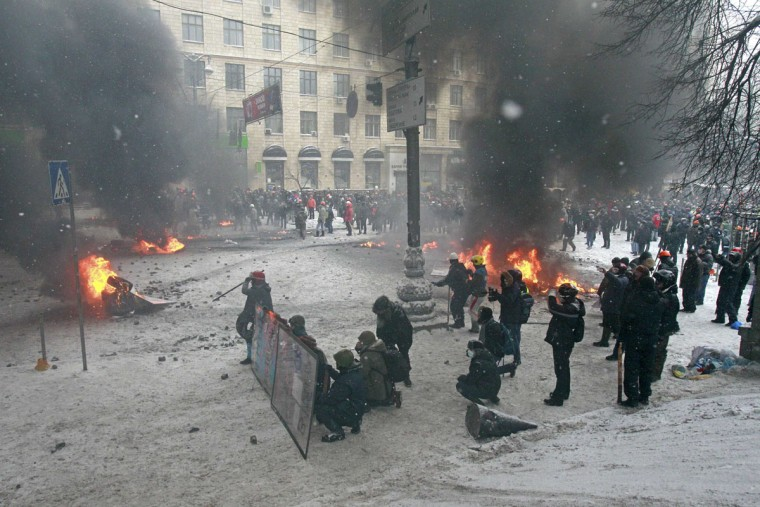 Pro-European protesters are seen near burning tyres during clashes with riot policemen in Kiev January 22, 2014. The European Union threatened on Wednesday to take action against Ukraine over its handling of anti-government protests after three people died during violent clashes in Kiev. (REUTERS/Gleb Garanich)