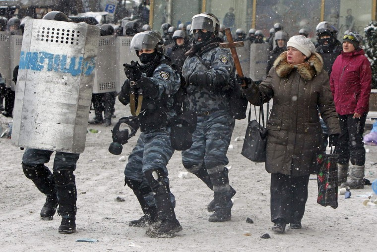 "A woman holds a wodden cross as riot policemen aim their weapons during clashes with pro-European protesters in Kiev January 22, 2014. Ukraine's prime minister denounced anti-government protesters as ""terrorists"" on Wednesday, but in what appeared to be his first real move to end weeks of unrest President Viktor Yanukovich held talks with opposition leaders. (REUTERS/Gleb Garanich)"