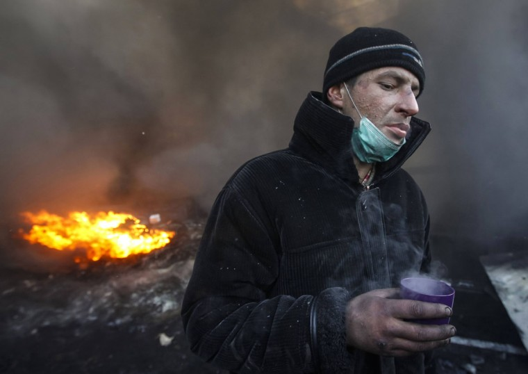 A pro-European integration protester drinks near burning tyres at the site of clashes with riot police in Kiev January 23, 2014. Ukrainian opposition leaders emerged from crisis talks with President Viktor Yanukovich on Wednesday saying he had failed to give concrete answers to their demands, and told their supporters on the streets to prepare for a police offensive. (REUTERS/Vasily Fedosenko)