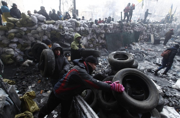 Anti-government protesters take tyres at a barricade at the site of clashes with riot police in Kiev January 25, 2014. Ukrainian President Viktor Yanukovich, in what appeared to be an offer of concessions to the opposition amid violent protests against his rule, pledged on Friday to reshuffle the government next week and to amend sweeping anti-protest laws. (REUTERS/Vasily Fedosenko)