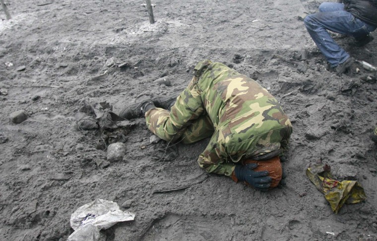 "A pro-European protester lies on the ground during clashes with riot police in Kiev January 22, 2014. Two demonstrators were on Wednesday reported killed in new anti-government unrest in the Ukrainian capital Kiev, inflaming protesters who confronted police shouting ""Murderers"" and ""Glory to Ukraine!"" (REUTERS/Gleb Garanich)"