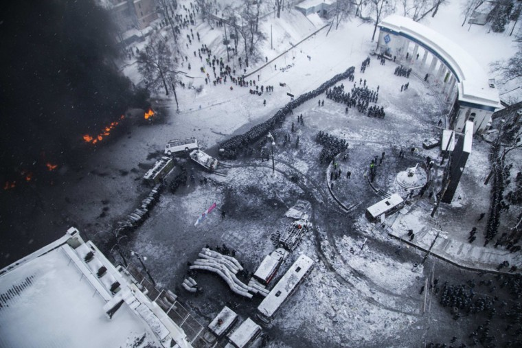 "An aerial view shows riot police and Interior Ministry members standing in formation as tyres set ablaze by pro-European protesters burn during clashes in Kiev January 22, 2014. Ukraine's prime minister denounced anti-government protesters as ""terrorists"" on Wednesday, but in what appeared to be his first real move to end weeks of unrest President Viktor Yanukovich held talks with opposition leaders. (REUTERS/Stringer)"