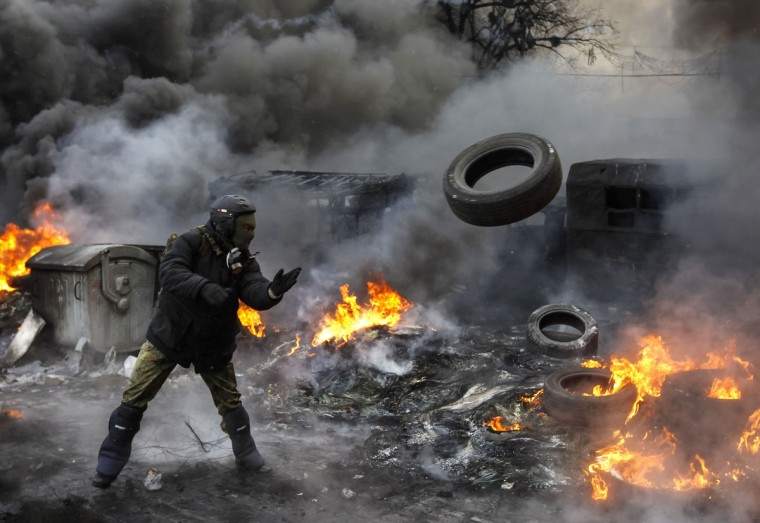 A pro-European integration protester throws a tyre at the site of clashes with riot police in Kiev January 23, 2014. Ukrainian opposition leaders emerged from crisis talks with President Viktor Yanukovich on Wednesday saying he had failed to give concrete answers to their demands, and told their supporters on the streets to prepare for a police offensive. (REUTERS/Vasily Fedosenko)