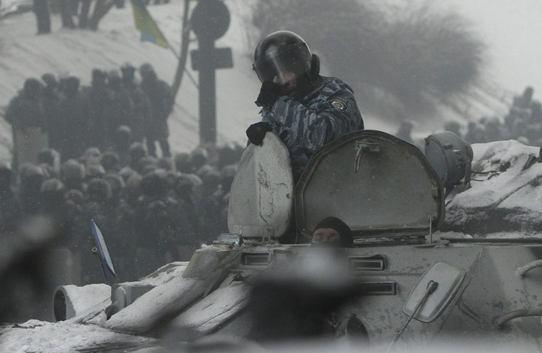Riot police officers look out from an armoured vehicle during clashes with pro-European protesters in Kiev January 22, 2014. Ukraine opposition leaders said on Wednesday there had been no concrete results from their talks with President Viktor Yanukovich to end weeks of street unrest and they called on protesters to prepare for a police offensive against them. (REUTERS/Stringer)
