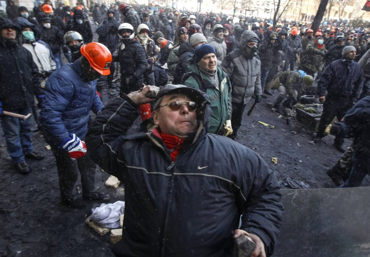 A pro-European integration protester throws stones towards riot police in Kiev January 23, 2014. Ukrainian opposition leaders emerged from crisis talks with President Viktor Yanukovich on Wednesday saying he had failed to give concrete answers to their demands, and told their supporters on the streets to prepare for a police offensive. (REUTERS/Vasily Fedosenko)