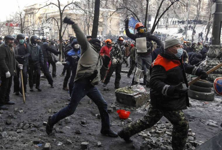 Pro-European integration protesters throw stones towards riot police in Kiev January 23, 2014. Ukrainian opposition leaders emerged from crisis talks with President Viktor Yanukovich on Wednesday saying he had failed to give concrete answers to their demands, and told their supporters on the streets to prepare for a police offensive. (REUTERS/Vasily Fedosenko)