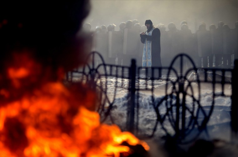 A priest prays in front of riot police during clashes with anti-government protesters in Kiev January 25, 2014. Ukrainian President Viktor Yanukovich, in what appeared to be an offer of concessions to the opposition amid violent protests against his rule, pledged on Friday to reshuffle the government next week and to amend sweeping anti-protest laws. (REUTERS/Antti Aimo-Koivisto/Lehtikuva)