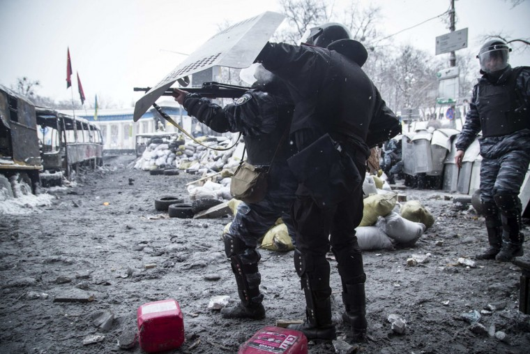 "A riot police officer points his weapon during clashes with pro-European protesters in Kiev January 22, 2014. Ukraine's prime minister denounced anti-government protesters as ""terrorists"" on Wednesday, but in what appeared to be his first real move to end weeks of unrest President Viktor Yanukovich held talks with opposition leaders. (REUTERS/Stringer)"