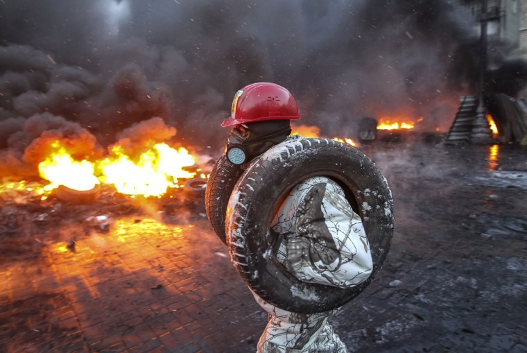 A pro-European integration protester carries tyres for burning at the site of clashes with riot police in Kiev January 23, 2014. Ukrainian opposition leaders emerged from crisis talks with President Viktor Yanukovich on Wednesday saying he had failed to give concrete answers to their demands, and told their supporters on the streets to prepare for a police offensive. (REUTERS/Valentyn Ogirenko)