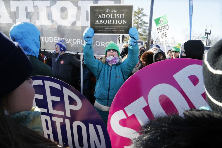 An anti-abortion demonstrator (C) shouts at pro-choice demonstrators in front of the U.S. Supreme Court during the annual March for Life in Washington, January 22, 2014. Pope Francis used Twitter to back the annual anti-abortion rally, which was expected to draw tens of thousands of activists to Washington on Wednesday. (REUTERS/Jonathan Ernst)