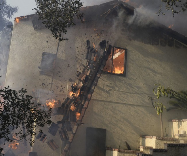 "Homes are engulfed in flames, as firefighters battle a fast-moving California wildfire, so-called the ""Colby Fire"", in the hills of Glendora January 16, 2014. The wildfire, started accidentally by three campers, roared out of control in foothills above Los Angeles on Thursday, destroying at least two homes and forcing more than 1,000 residents to flee, fire and law enforcement officials said. The wind-whipped blaze erupted before dawn in the Angeles National Forest north of Glendora, about 40 miles east of downtown Los Angeles in the foothills of the San Gabriel Mountains. (REUTERS/Gene Blevins)"