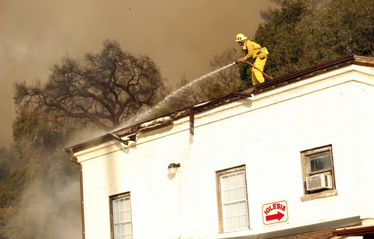 A firefighter hoses water as he defends a structure during the Colby Fire in hills above Glendora, California January 16, 2014. The fire began early Thursday morning and has so far scorched 125 acres. (REUTERS/Mario Anzuoni)