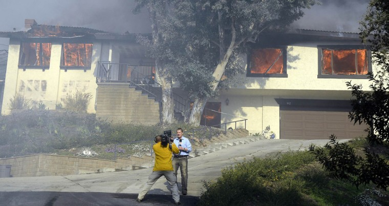 "Homes are engulfed in flames, as media reports on the so-called the ""Colby Fire"", in the hills of Glendora January 16, 2014. The wildfire, started accidentally by three campers, roared out of control in foothills above Los Angeles on Thursday, destroying at least two homes and forcing more than 1,000 residents to flee, fire and law enforcement officials said. The wind-whipped blaze erupted before dawn in the Angeles National Forest north of Glendora, about 40 miles east of downtown Los Angeles in the foothills of the San Gabriel Mountains. REUTERS/Gene Blevins"