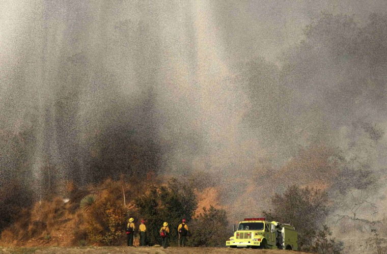 Firefighters stand as water falls from a firefighting aircraft on the Colby Fire in Azusa, California January 16, 2014. The blaze broke out about an hour before sunrise in the Angeles National Forest north of Glendora and quickly spread to 1700 acres. Glendora is located about 40 miles (64 km) east of downtown Los Angeles, near the southern edge of the Angeles National Forest. REUTERS/Jonathan Alcorn