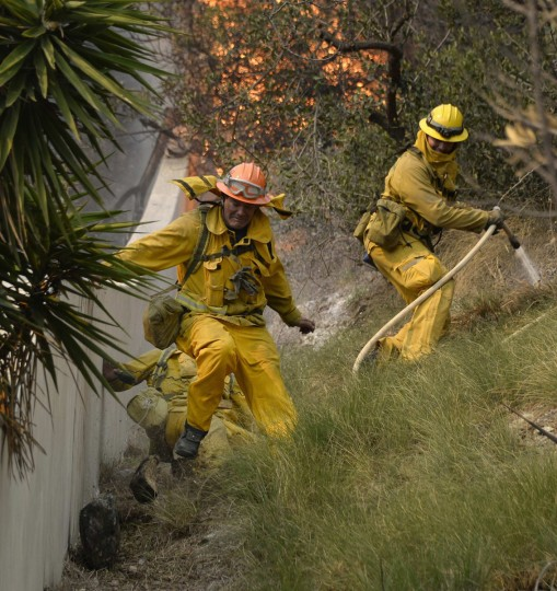 "Firefighters are hit by heavy boulders rolling downhill, with one suffering a broken ankle, as they battle a fast-moving California wildfire, so-called the ""Colby Fire"", in the hills of Glendora January 16, 2014. The wildfire, started accidentally by three campers, roared out of control in foothills above Los Angeles on Thursday, destroying at least two homes and forcing more than 1,000 residents to flee, fire and law enforcement officials said. The wind-whipped blaze erupted before dawn in the Angeles National Forest north of Glendora, about 40 miles east of downtown Los Angeles in the foothills of the San Gabriel Mountains. (REUTERS/Gene Blevins)"