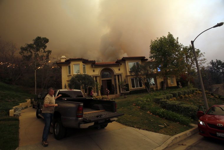 Residents evacuate their home as the Colby Fire approaches in hills above Glendora, California January 16, 2014. The fire began early Thursday morning and has so far scorched 125 acres. (REUTERS/Mario Anzuoni)
