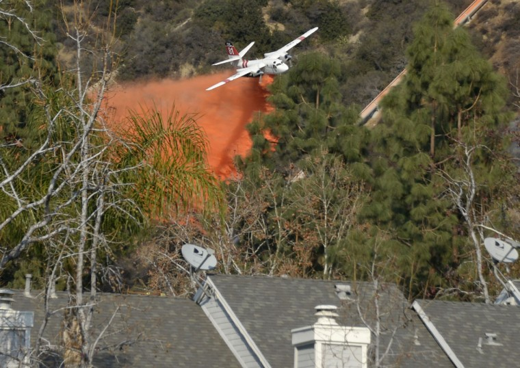 "An air tanker makes waters drops as firefighters battle a fast-moving California wildfire, so-called the ""Colby Fire"", in the hills of Glendora January 16, 2014. The wildfire, started accidentally by three campers, roared out of control in foothills above Los Angeles on Thursday, destroying at least two homes and forcing more than 1,000 residents to flee, fire and law enforcement officials said. The wind-whipped blaze erupted before dawn in the Angeles National Forest north of Glendora, about 40 miles east of downtown Los Angeles in the foothills of the San Gabriel Mountains. (REUTERS/Gene Blevins)"