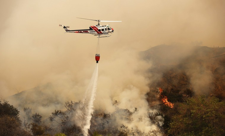 A helicopter makes a water drop on the Colby Fire in Glendora, California January 16, 2014. The blaze broke out about an hour before sunrise in the Angeles National Forest north of Glendora and quickly spread to 1700 acres. Glendora is located about 40 miles east of downtown Los Angeles, near the southern edge of the Angeles National Forest. (REUTERS/Mario Anzuoni)