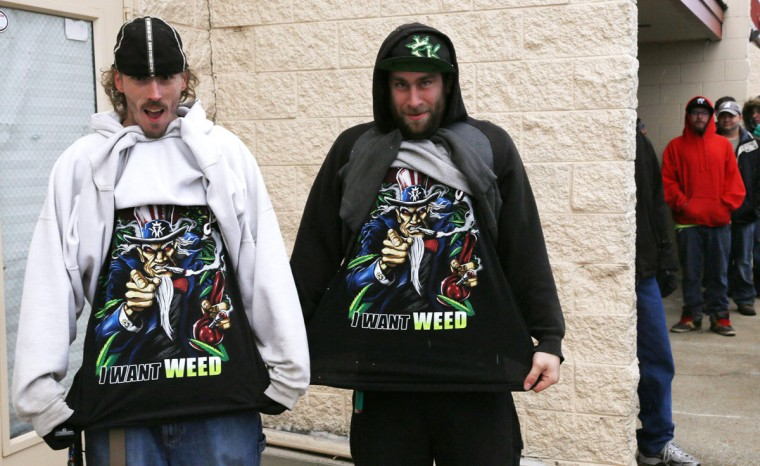 "Mark Gordon, left, and Ryan Perry display their ""I Want Weed"" T-shirts as they wait in line to be among the first to legally buy recreational marijuana at the Botana Care store in Northglenn, Colo., on Jan. 1, 2014. (Rick Wilking/Reuters)"