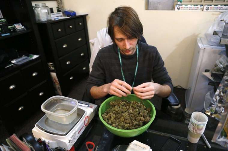 Skylar Hall prepares marijuana buds for sale at the Botana Care marijuana store ahead of their grand opening on New Year's Day in Northglenn, Colo. (Rick Wilking/Reuters)