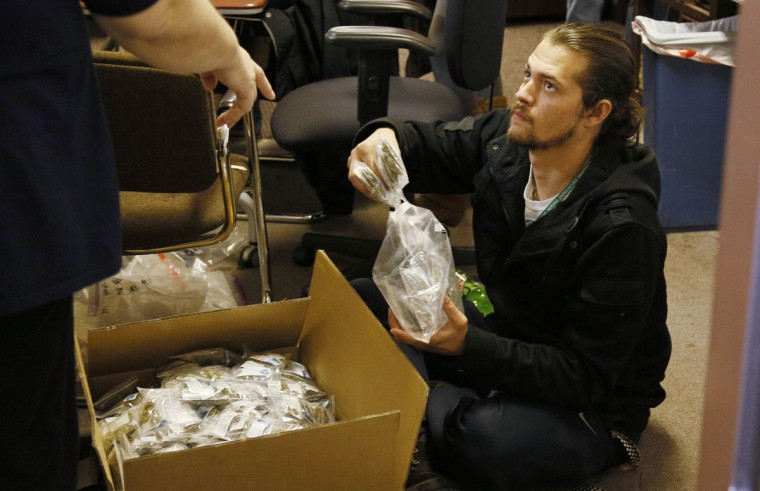 Troy McIntyre, a worker at BotanaCare, organizes bags of the company's sample packs of various strains of marijuana prepared for the store opening in Northglenn, Colo. (Rick Wilking/Reuters)