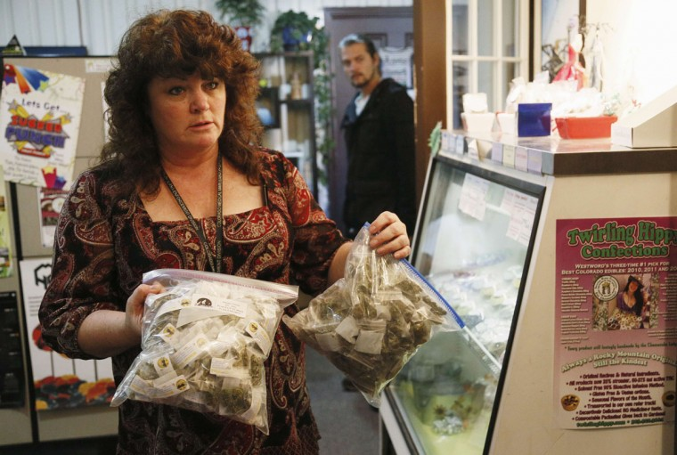 Cheri Hackett, co-owner of BotanaCare, carries bags of the company's sample packs of various strains of marijuana prepared for the store opening in Northglenn, Colo. (Rick Wilking/Reuters)
