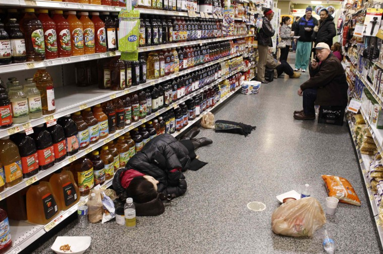 People rest at the aisle of a Publix grocery store after being stranded due to a snow storm in Atlanta, Georgia, January 29, 2014. A rare winter storm gripped the U.S. South on Wednesday, killing five people, stranding children overnight at their schools, gnarling traffic across many states and canceling flights at the world's busiest airport. (Tami Chappell/Reuters)