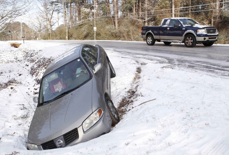 A driver uses a mobile phone in a car after running off the roadway due to a snow storm in Atlanta, Georgia, January 29, 2014. A rare winter storm gripped the U.S. South on Wednesday, killing five people, stranding children overnight at their schools, gnarling traffic across many states and canceling flights at the world's busiest airport. (Tami Chappell/Reuters)