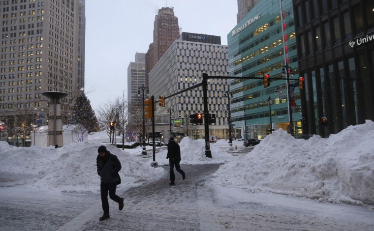 Pedestrians walk past mounds of snow during bitter cold temperatures in downtown Detroit. (REUTERS/Rebecca Cook)
