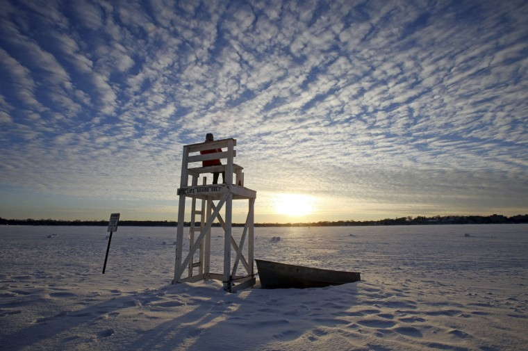 Jennifer Berry watches the sunset from a lifeguard chair at a beach on Lake Calhoun in Minneapolis. Shortly after daybreak Tuesday in the Twin Cities, thermometers had inched their way up to anywhere from 8 to 13 below zero. The National Weather Service (NWS) said Tuesday's high is expected to be near zero. A deadly blast of arctic air shattered decades-old temperature records as it enveloped the eastern United States on Tuesday, snarling air, road and rail travel, driving energy prices higher and overwhelming shelters for homeless people. At least eight deaths have been reported across the country because of the polar air mass sweeping over North America during the past few days. Authorities have put about half of the United States under a wind chill warning or cold weather advisory. (Eric Miller/Reuters)